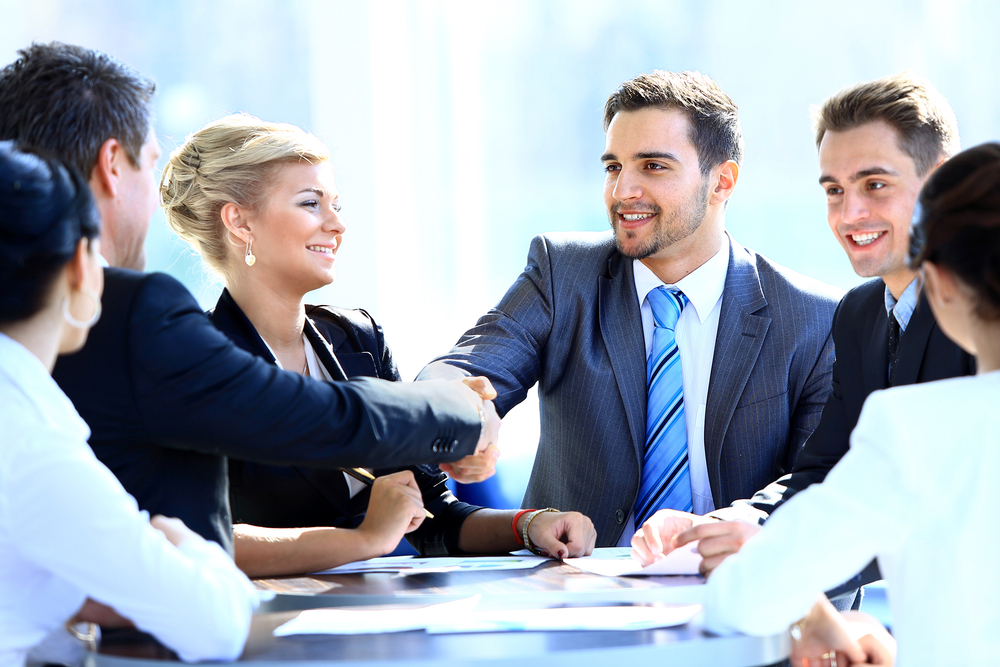 Real estate investor shaking hands with associates
