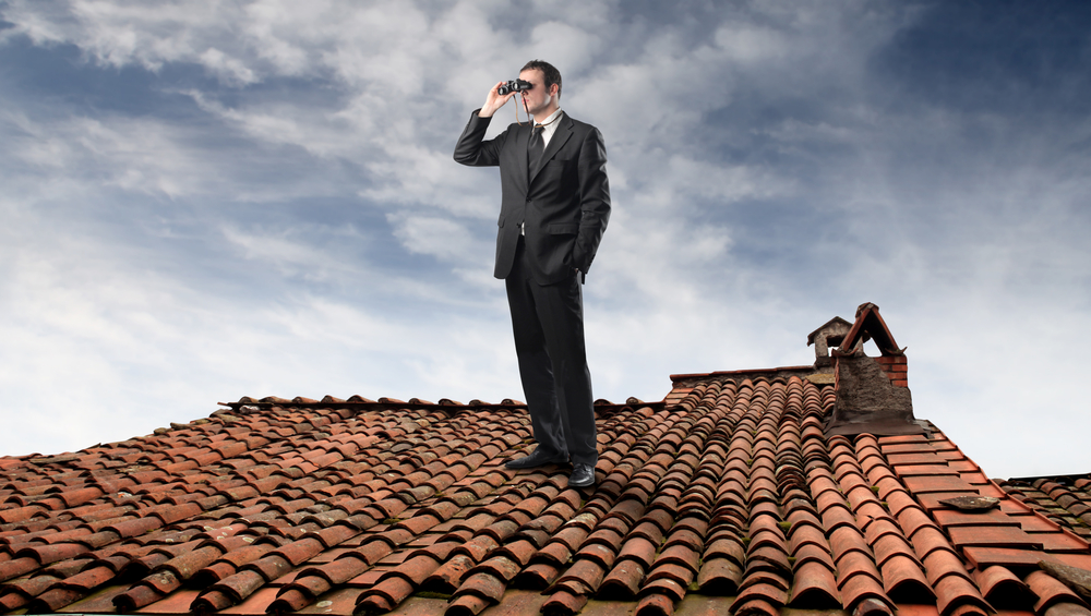 Man with binoculars on rooftop