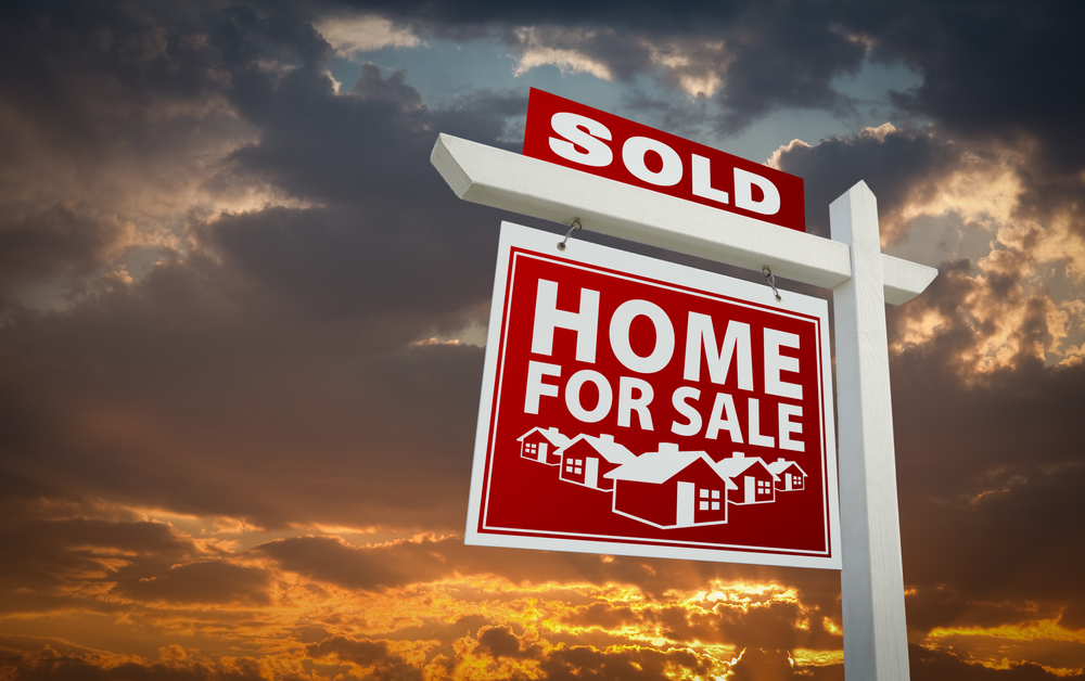 Home sold sign with cloudy background