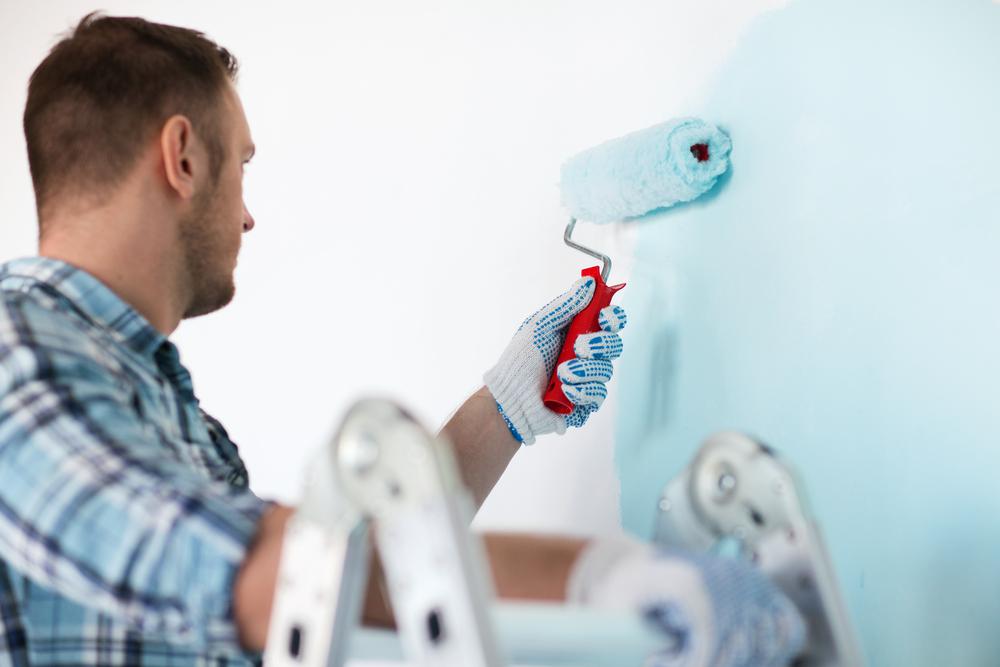 Man painting a wall light blue
