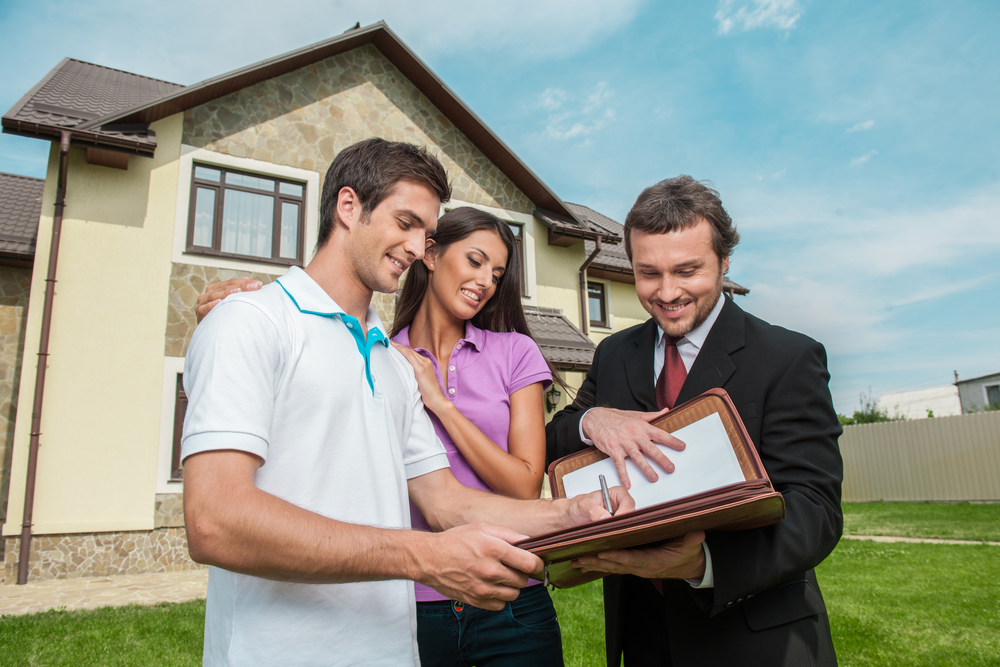 Young coouple signing home mortgage papers