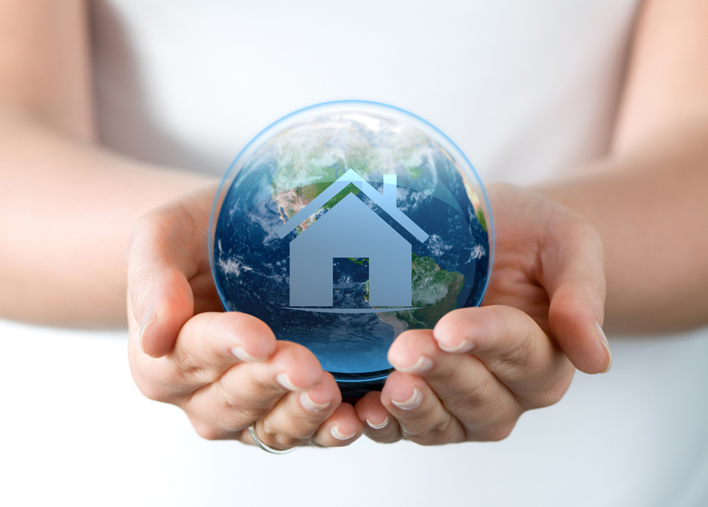 Hands holding the world with house icon